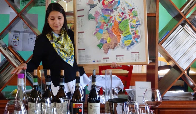 Lady showing map of terroir and wine bottles on table