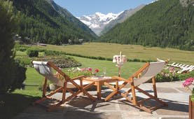 Terrace area with wooden deckchairs laid out, overlooking a green lawn and the italian alps, with snow-topped mountains far away