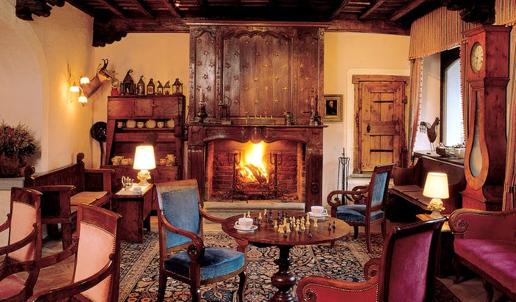 Cosy indoor lounge area with fire place, arm chairs, chess board on the table and old fashioned wooden deocrations