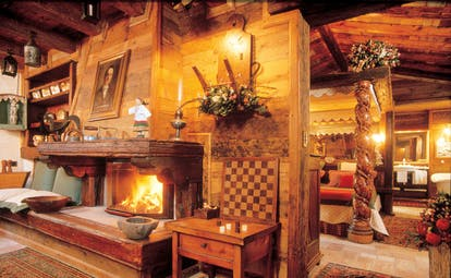 Suite with wood pannelled walls, paintings on the walls, an open fireplace, bedroom and old fashioned decor
