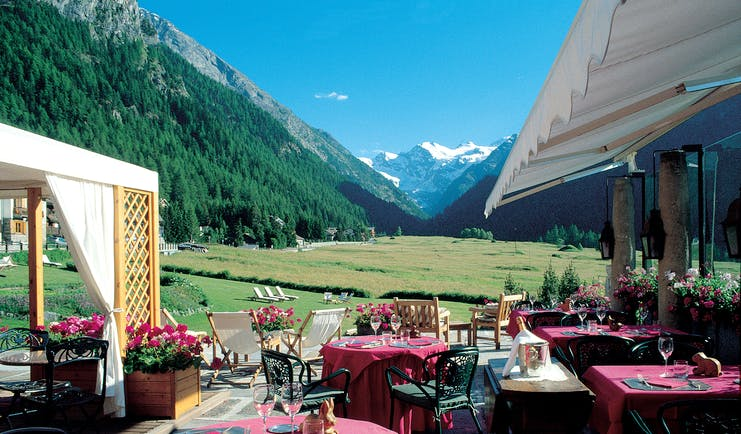 Outdoor dining terrace with views of snowy peaks and tables and chairs set out ready for a meal