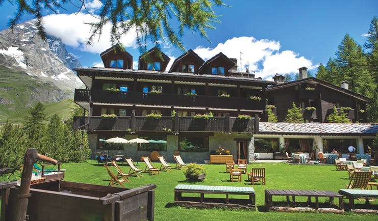 Hotel Hermitage Italy Alps exterior  green lawn out door seating mountain in background