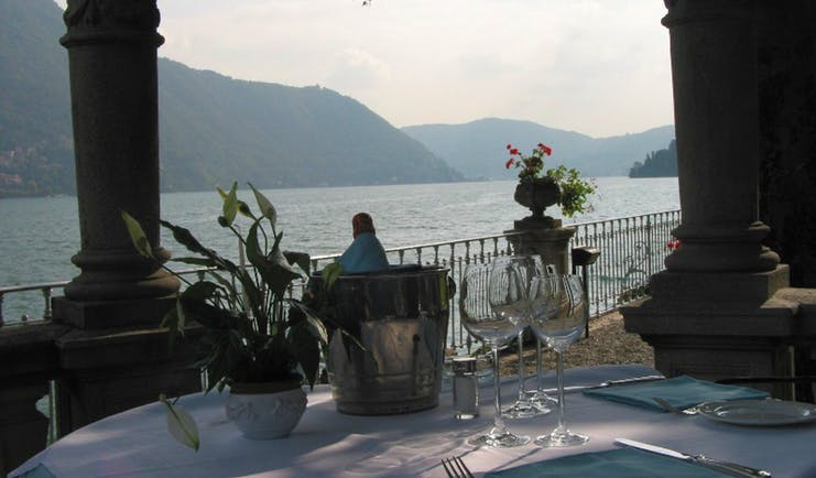 Table set up for dining near to lake with view of water and mountains