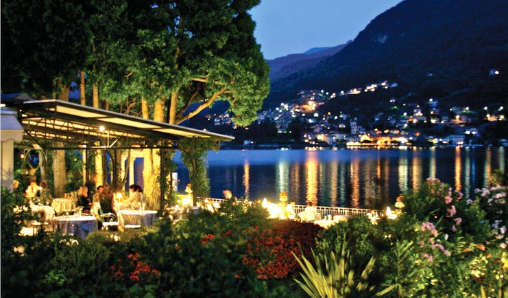 Night time view of the outdoor restaurant all lit up with yellow lights and looking over the lake