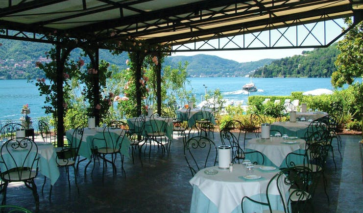 Restaurant with outdoors seating area covered by porch with tables and chairs set up with view of lake