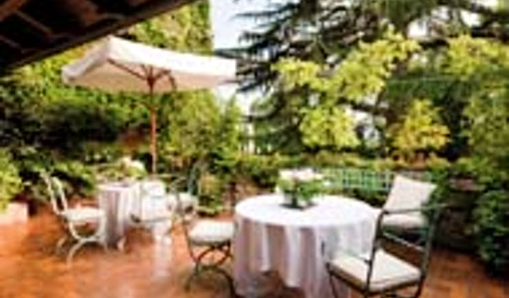 Hotel L'Albereta Lake Iseo terrace outdoor dining area tables chairs trees
