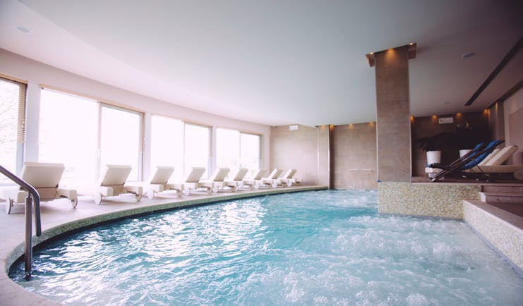 Hotel Olivi indoor pool with jacuzzi area, white sunbeds laid out around the pool