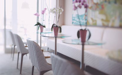 Hotel Olivi lounge and bar with white seats, small clear coffee tables with purple flowers on