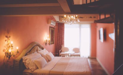 Red themed bedroom with large double bed, red curtains and chandeliers