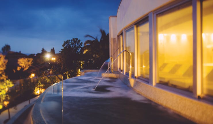 View of the thermal pool at dusk with lights lit up and water being sprayed into the pool