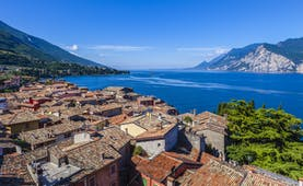 Aerial view of the terracotta roofs of the houses of Malcesine village on shore of deep blue Lake Garda