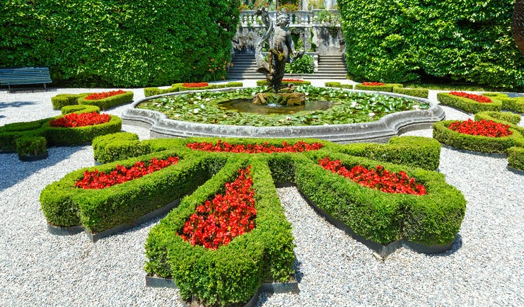 Formal flower beds of red lined with green box in parterre of villa carlotta on Lake Como