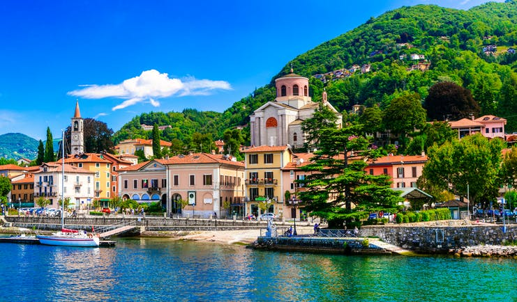 Village with church and houses with red roofs lining the waterfront of Lake Maggiore