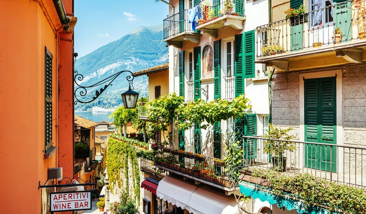 Houses with balconies and green shutters and vines overlooking Lake Como in Bellagio