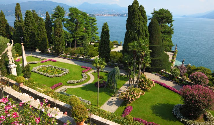 Terraced grassy gardens and stone walls with red flowers overlooking lake como