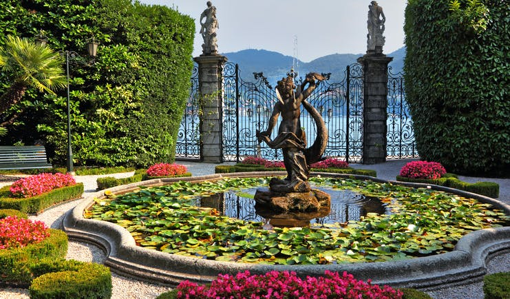 Fountain and pond with water lilies and pots of red flowers by gate at Villa Carlott on Lake Como