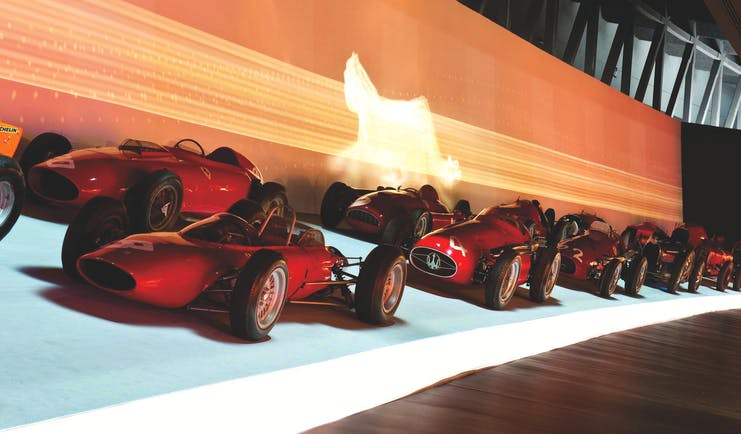 Row of red racing cars in museum