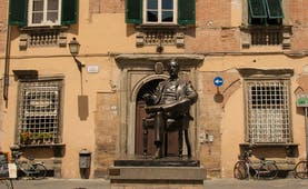 Statue of composer Puccini in front of punk and green building in Lucca