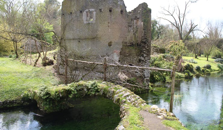 Ruined medieval building with footbridge over river in foreground