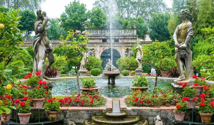 Statues, red flowers, fountains and water features at Palazzo Pfanner Tuscany