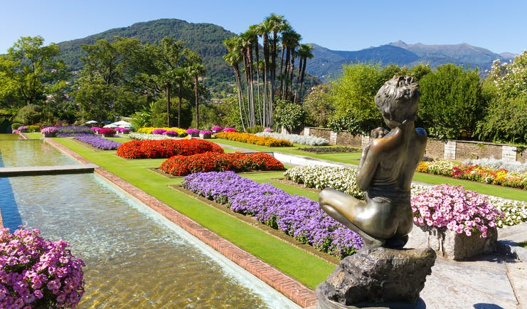 Statue of girl overlooking water feature flanked by red and purple flowers at Villa Taranto Lake Maggiore