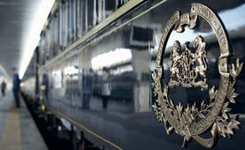Shiny blue train at platform with silver logo on side