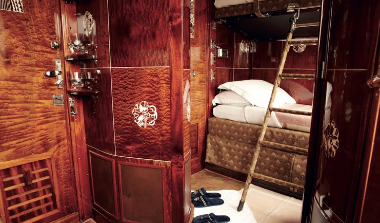 Dark shiny wooden railway cabin with bed and ladder on Orient Express