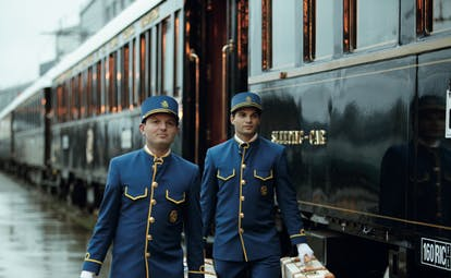 Two porters in blue uniform carrying suitcases on the Orirent Express