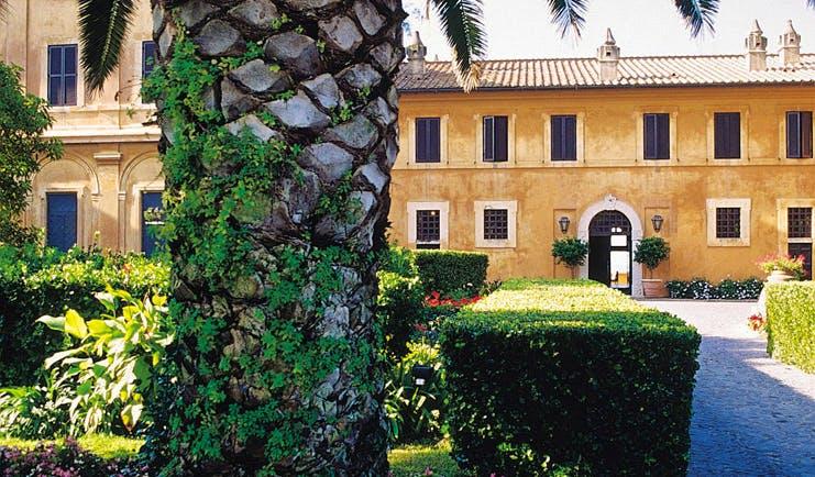 La Posta Vecchia Latium pathway leading to hotel tree shrubs building