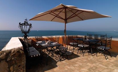 La Posta Vecchia Latium terrace tables chairs umbrella overlooking sea