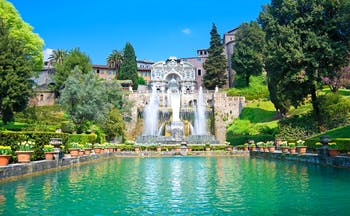 Turquoise pond with jets of water from fountains with terraced stone landscape and trees at Villa d'Este Tivoli near Rome