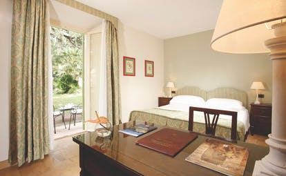 Vila Grazioli Latium charme deluxe room bedroom leading out to garden and outdoor seating area