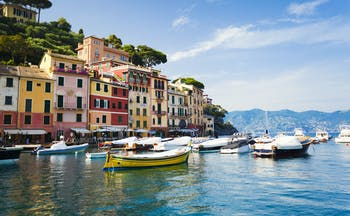 Small colourful boats in harbour water with houses of red and ochre in Portofino
