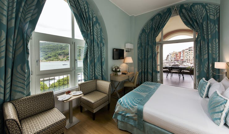 Cloister junior suite with blue colour scheme, large double bed, arm chairs and double doors opening out onto terrace balcony with views over ocean and city
