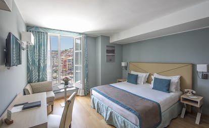 Executive room with blue colour scheme, large double bed, double doors opening out onto balcony and television