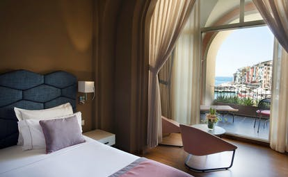 Junior suite with double bed, arm chairs and doors opening onto a terrace areas with views over city and ocean