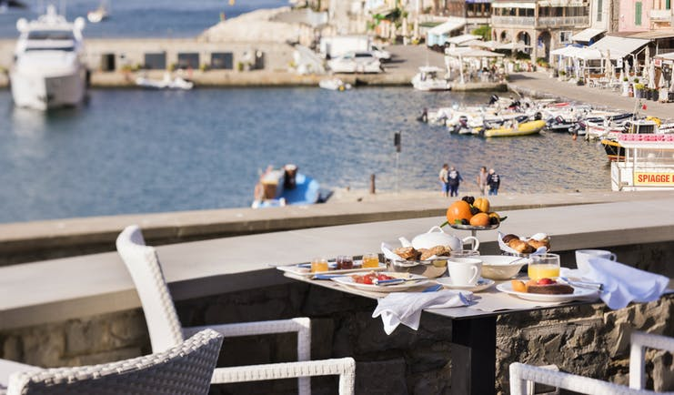 Breakfast laid out on tables outdoors on terrace with views of port