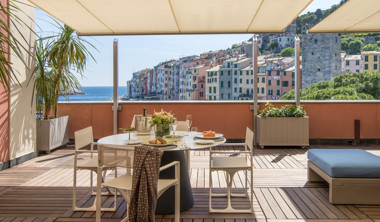 Terrace outdoor covered dining area with tables and chairs set out on wooden decking with views over ocean and colourful  buildings