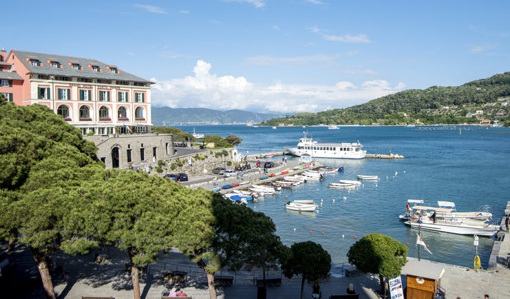 Building of hotel on a slight hill overlooking a port with hills in the distance at the Grand Hotel Portovenere