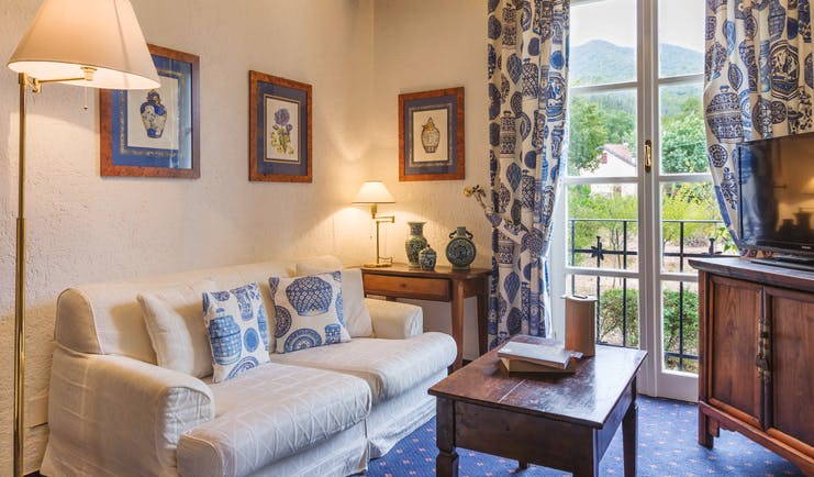 Sofa and lamps, blue and white scheme, with French window behind at La Meridiana