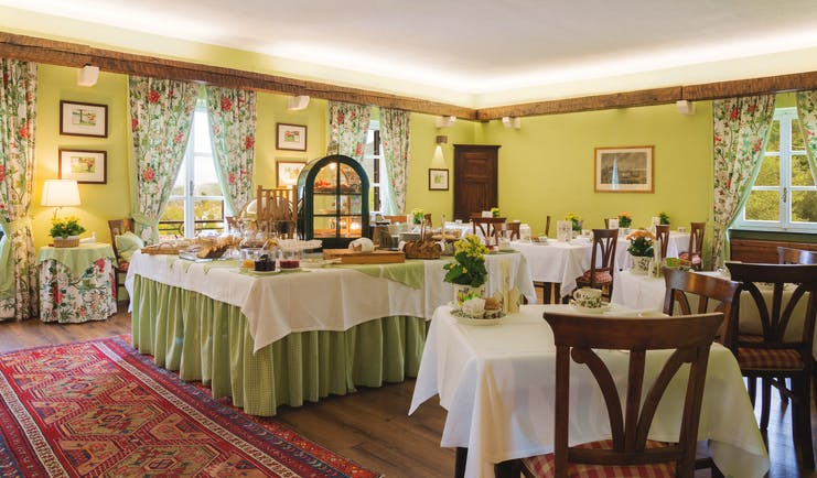Green coloured walls and red rug with tables covered with white table cloths laid for breakfast at La Meridiana