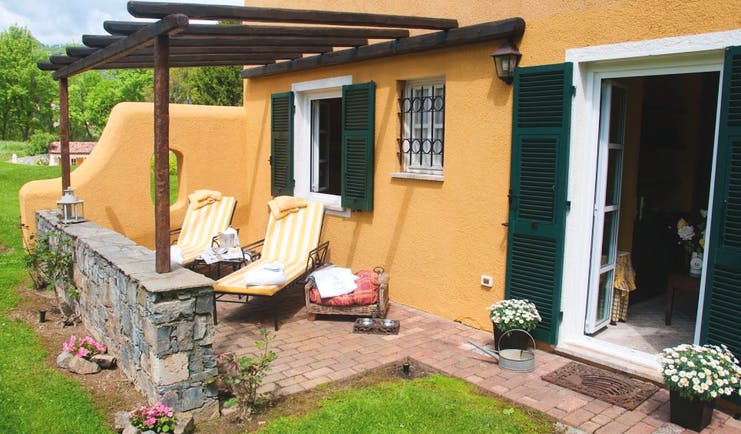 Garden patio with lounger chairs and grass outside open French window with green shutters at La Meridiana