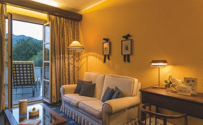 Sofa and balcony with open door, yellow walls and lamps on at La Meridiana