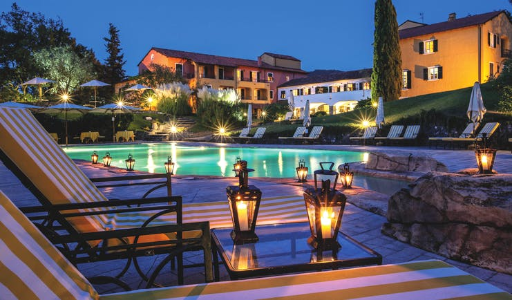 Pool with illuminated hotel buildings at night with cypress trees and lanterns on tables at La Meridiana Liguria