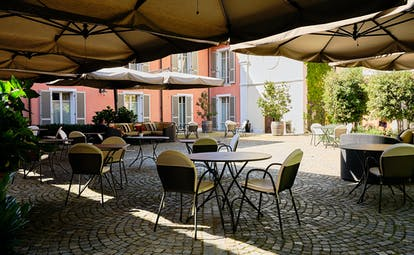 Villa D'Amelia Piemonte cobbled patio with tables and chairs and sunshades