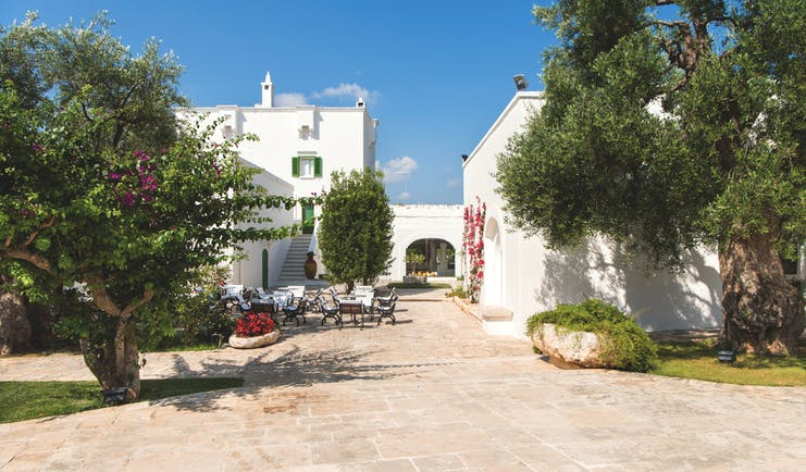 Il Melograno Puglia exterior white building outdoor dining area trees
