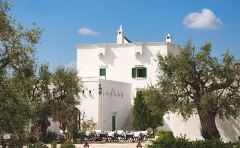 Il Melograno Puglia hotel exterior white building trees outdoor dining area