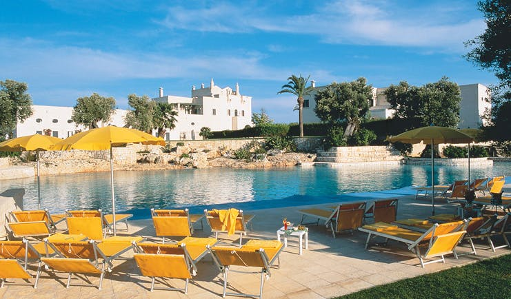 Masseria San Domenico Puglia poolside sun loungers umbrellas hotel in background