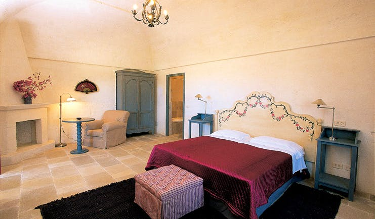 Masseria Torre Coccaro Puglia superior room bed fireplace wardrobe elegant décor