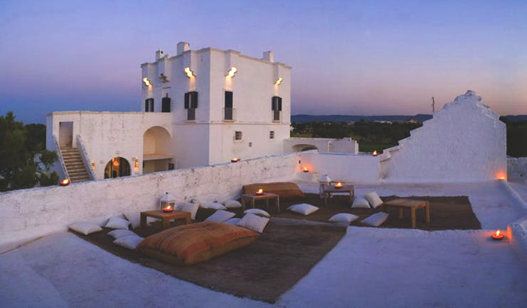 Masseria Torre Maizza Puglia rooftop terrace at night floor cushions rugs candle lights